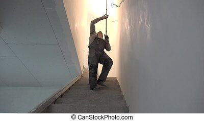 Worker Painting Ceiling With Roller in staircase. Tilt up...