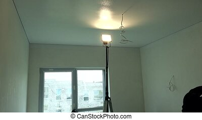 Worker Painting Ceiling With Roller. Man paints white...