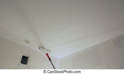 Worker painting ceiling with white paint