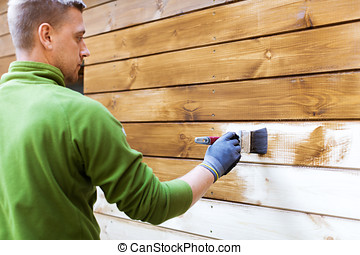 worker painting house exterior with brown wood protective color