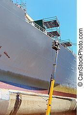 Worker painting ship hull using airbrush.