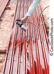 Worker painting steel bar.