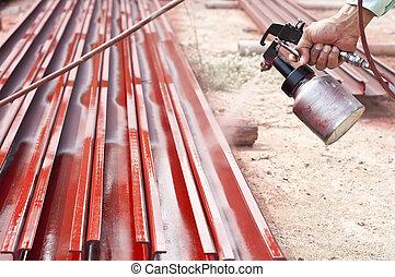 Worker painting steel bars.