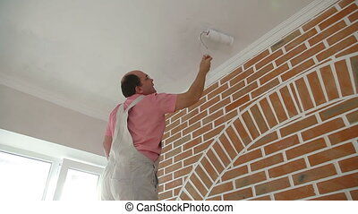 Worker painting the ceiling