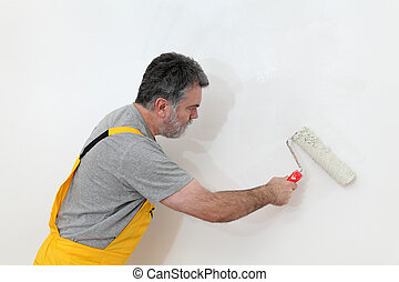 Worker painting wall in room