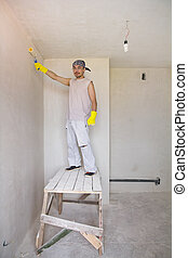 Worker painting wall with painting roller