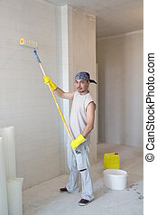 Worker painting wallpaper