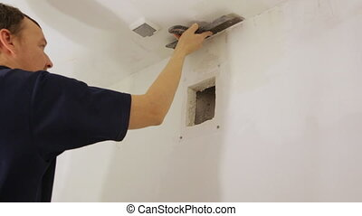 Worker plastering a ceiling with trowel