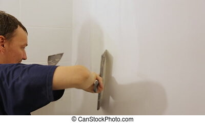 Worker plastering a wall with trowel