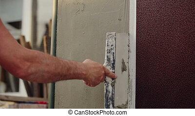 Worker Plastering Wall - Worker plastering wall of house