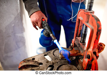worker, plumber using blowtorch for soldering copper...