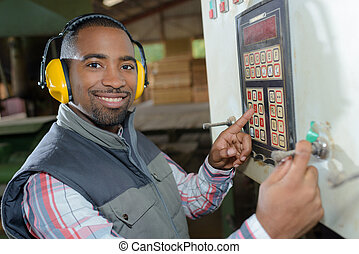 worker pointing at a machine button