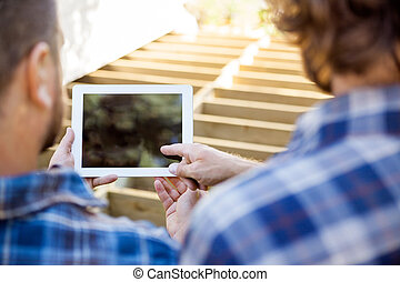 Cropped image of worker pointing at digital tablet while coworker holding it