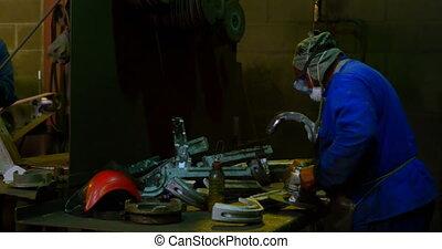 Worker polishing metal casting in foundry workshop 4k - ...