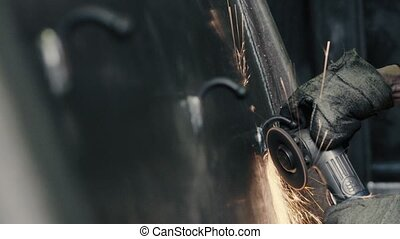 Worker polishing metal parts in industrial plant - Close up...