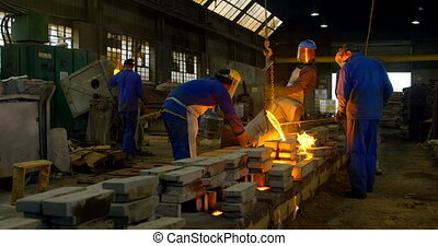 Worker pouring molten metal from container in foundry workshop 4k
