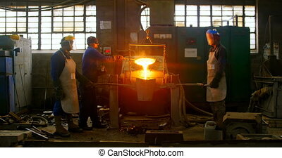 Worker pouring molten metal in container 4k