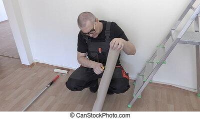 Worker prepare paper before wall painting