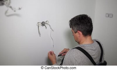 Worker prepare wires to connect socket rosette frames in...