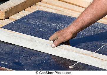 Worker preparing plank for cutting