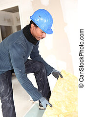 Worker preparing wall insulation
