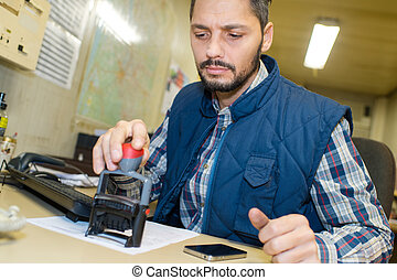worker pressing a stamp on document in the office