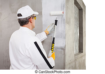 Worker priming with a paint roller