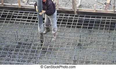 Worker pulling a large hose for concreting of steel ...