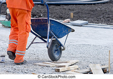 Worker pushing cart - Construction worker pushing carts with...
