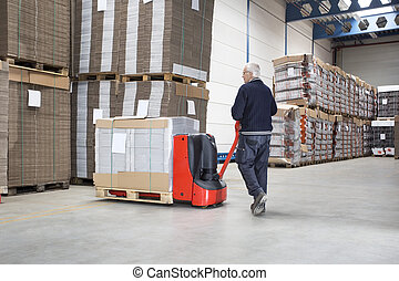 Worker Pushing Handtruck Loaded With Goods - Rear view of...