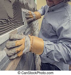 Worker pushing the tile into the cement on the wall