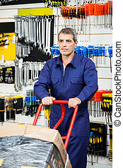 Worker Pushing Trolley In Hardware Shop