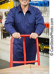 Worker Pushing Trolley In Hardware Store