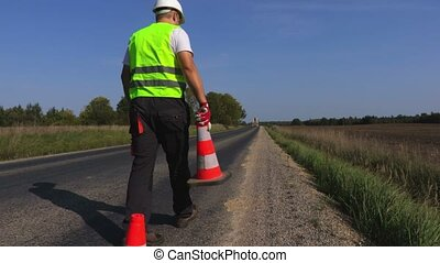 Worker put cones on the edge of highway