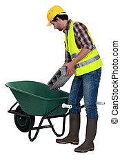 Worker putting a concrete block into a wheelbarrow