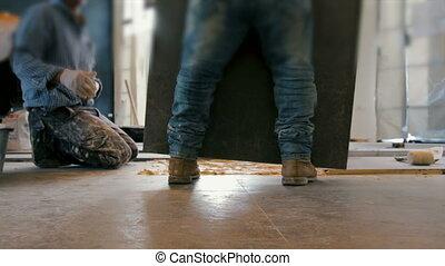 Worker putting ceramist tile on the floor.