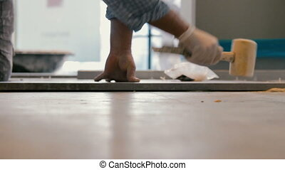 Worker putting ceramist tile on the floor. He presses the...