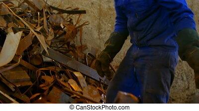Worker putting metal in wheelbarrow in foundry workshop 4k...