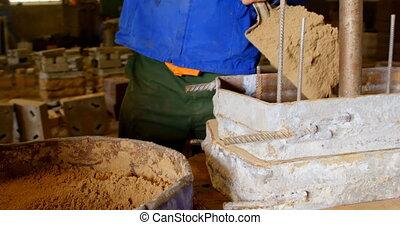 Worker putting soil in molds in foundry workshop 4k - Worker...