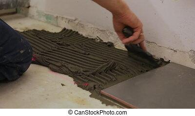 Worker putting tile glue on floor