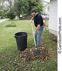 Worker Raking Leaves For Customer