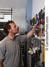 worker reaching for tool at wall