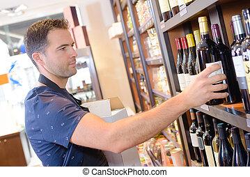 Worker refilling shelf with wine bottles