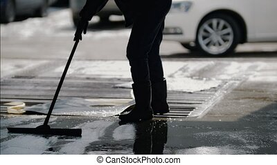 Worker remove foam and water with a MOP after car washing