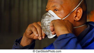 Worker removing mask in foundry workshop 4k - Worker ...