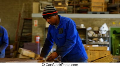 Worker removing metal rod from molds in workshop 4k - Worker...