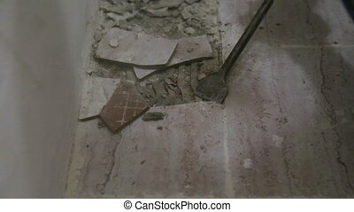 Worker removing old tile from the floor in bathroom