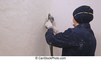 Worker removing surface cover from the wall