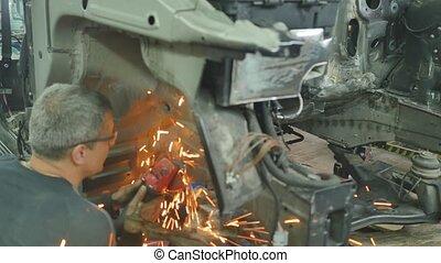 Worker repairing car body in garage