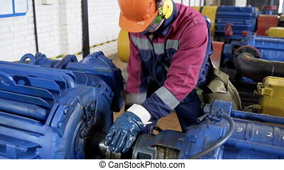 Worker repairing pipelinein pump station at oil production...